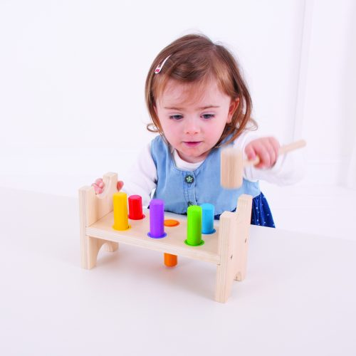 toddler playing with a wooden hammer bench