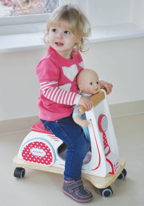 child on a wooden retro scooter